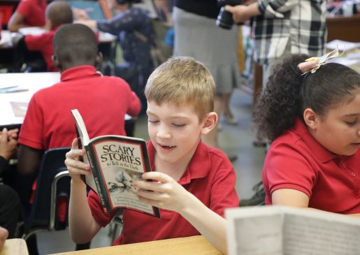 A student reads a book he just received from Book Trust