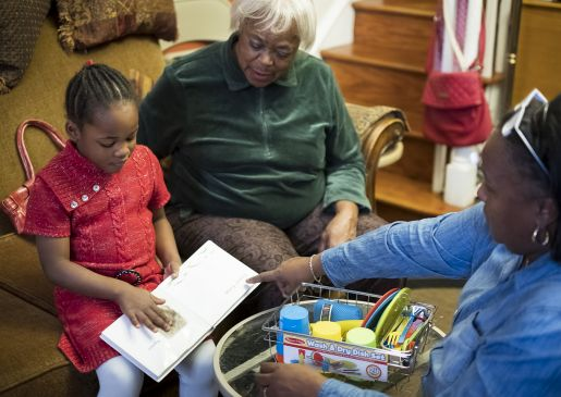 a child reads with her grandmother and home visitor