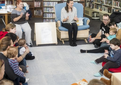 A group of caregivers and infants have a sing along at the local library branch.