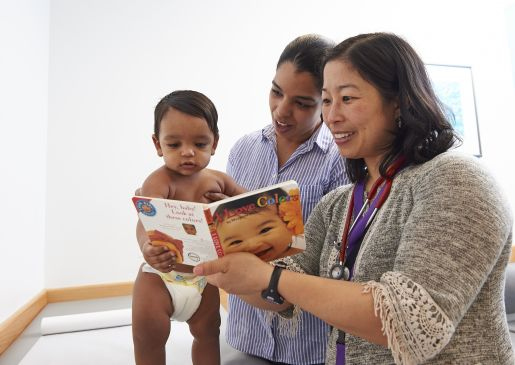 A doctor gives a book to a mother and infant son.